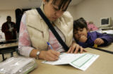 At the Colorado Department of Human Services in east Denver, Maria Alcala (cq) fills out a form...