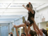 Members of the Evergreen High School Cheerleader Squad lift cheerleader Megan Bomgaars in to the...