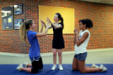 Cheerleaders Natalie Scholander (cq), left, and Kaire Phelps (cq), right, help Megan Bomgaars...
