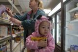McKenna McPhail, 2, holds a box of cookie mix, while her grandmother Lisa Post (cq) does some...
