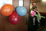 Chris  Sauser carries his daughter Juliana out of a ballon decorated courtroom Friday November 2,...
