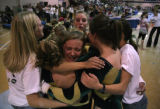 At the Girls State Gymnastics Championship Bear Creek HS team members hug each other after their...