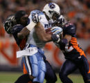 [JOE0074]  Denver Broncos Nate Webster, left, loses his helmet as he and Dominique Foxworth, (22)...