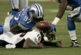 1488 Denver Broncos Brandon Marshall is tackled and forced to drop the ball by Detroit Lions Boss...