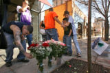 (from left) Dale Sasse (cq) lays some flowers at the scene where his friend, 25 year-old Theodore...