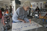 "Jeri Priest works on a "" Honk if your a Bronco fan"" sign in her garage, while her..."