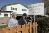 "Jeri Priest, left, watches herd husband Larry Priest (cq) put up a   "" Honk if your a Bronco..."
