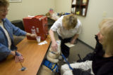 DM0832   Carolyn Griffin's service dog, Lena, hands her ballot over to election official Rose...