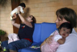 ABD101 - US citizens Emily Baures, 27, back, and Stephanie Rimmer, 41, play with the babies they...