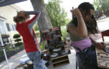 Mark Rinkel,12, left,pulls his hair back as he organizes a sale display of newly donated...