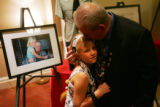 Sgt. 1st class retired Homer Galloway gives a kiss to his granddaughter Katie Staats, center, next...