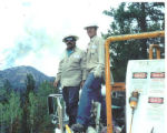 Andy Blood, right, poses for a photo while working on replacing utility lines after the Hayman...