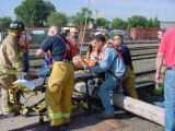 Rescue workers attend to Andy Blood after a utility pole he was working on snapped and he fell 25...
