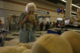 Doloris Dunn(cq) smells a cantaloupe as she shops at the Albertsons Shopping Center on Mississippi...
