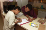 (Lakewood, Colo., October 1, 2004) Frankie Correa helps his son Adam Duncan, 9, with his homework...