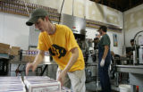 (Lyons, Colo., September 30, 2004) Adam Baron stacks boxes of beer after they have been finished...