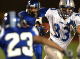 Thorton, Colo., photo taken October 1, 2004- Poudre High's Tyson Vogel (right #33) splits through...