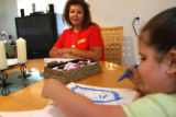 Teaching assistant Linda Ortega (cq) looks at the picture that 4 year-old Isabella Vergil draws...