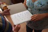 (from left) Stephanie Peterson (cq) looks over a penmanship's book used by Jessica Trujillo's (cq)...