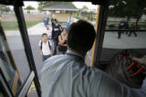 Aurora School District Superintendent John Barry(cq) steps off the buss to greet students on their...