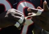#99 Alvin McKinley peels tape off his fingers at the end of  practice at the Denver Broncos...