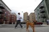 "Ky Johnson walks her dog ""biscuit"" in front of the new Benedict Park Place Apartments...."