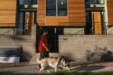 Mark Stabrawa (cq) walks his dog in front of a high-end apartment complex which is being built, on...