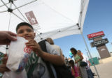 8 year-old Isaiah Espinoza (cq) receives a bag of popcorn after getting his new backpack for the...