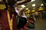 Daija Bell(cq), 7,  struggles to put on her new backpack with the help of her father Hardy(cq) at...