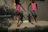 Twin sisters Jahkayla Lewis, 6, and Jahkiyla Lewis, 6, play outside of their home in Altgeld...