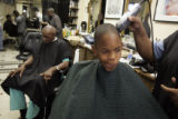 Nicholas Ivy, 8, tries to stop his nose from itching while his barber Naseem Majid (cq) trims his...