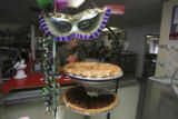 Lester Thorne, (cq) takes a phone order seen thru some pies and a mardi gras mask. His sister...