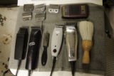 Barber Abdul Rahman's hair clippers and brushes are lined up on a tray in the Hyde Park Hair...