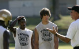 1742 Unidentified Little Rock Central High School football players listen to a coach during summer...