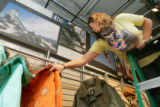 Lesley Betts (cq), 23, of lakewood, an employee of Burton, arranges snowboarding jackets in...