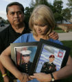 Mike and Deana Mobley (cq)hold photos of their twin sons, Ryan, left, who is in the Marines and...