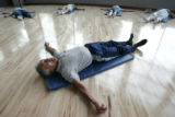Eddie Owada (cq) 81, leads his students, all senior citizens,  through stretches during a senior...