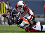 Denver Bronco's running back Selvin Young, left, stretches for the first down being defended by...