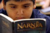 "6th grader, Denvonte Ramos (Cq) reads ""The Chronicles of Narnia"" at Mrs. Alethea..."