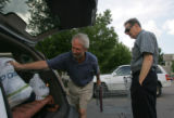 Hank Troy (cq), 60, left, loads grocieries in the back off the car while helping Arnie Langberg...
