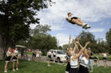 Monarch High School varsity cheerleader Katie McMenamin (cq), 16, prepares to land in the arms of...