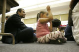 0427 Jaime Aquino, chief academic officer for the Denver Public Schools, left, sits on the floor...