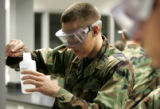 Freshman Air Force Cadet 4th class Austin Kootz, left, measures an unknown substance works on a...