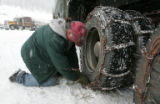 Herb Shippey, (cq)  from Missoula, Montana chains up his big rig in the parking lot of Loveland...