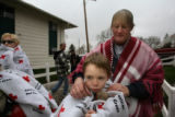 8 year-old Ryan Stinett (cq) is looked after by his neighbor, Sharon Andrews (cq) as they wait for...