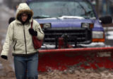 Brandi Gatlin (cq) walks along the 16th Street Mall, as a snow-plow removes the accumulation in...