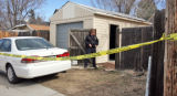 A Wheat Ridge Police Officer stands watch behind the home of Tyler James Martin (cq) in the 1300...