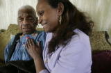 Louise Ellis, 95 sits with her  caregiver, Abeda Gebrehiwed, a CNA, in her Denver home Wednesday...