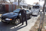 A Wheat Ridge Police Officer examines a black Ford with Illinois plate 6639238 as it is towed...