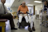 Donald Roberts takes a break after testing out his new prosthetic legs at Spalding Rehab Hospital...